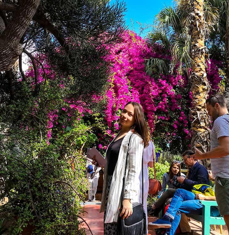 Girl posing in front of flowers at Jardin Majorelle in Marrakech