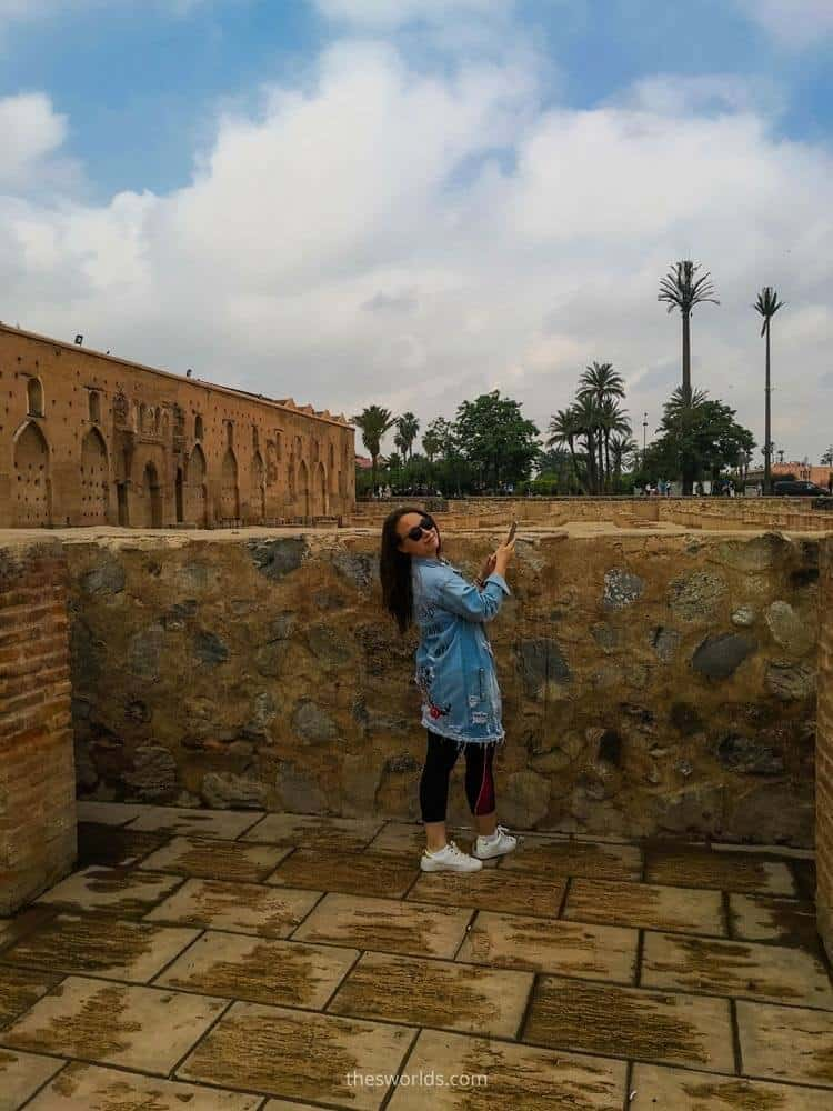 Girl taking a picture of ruins of Koutoubia in Marrakech