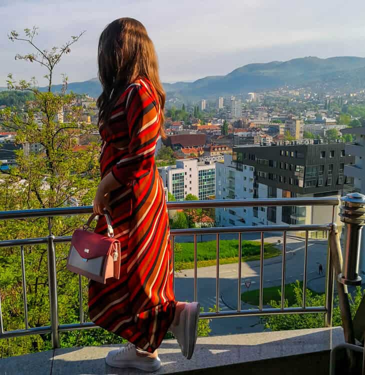 Girl standing at balcony and looking at Sarajevo