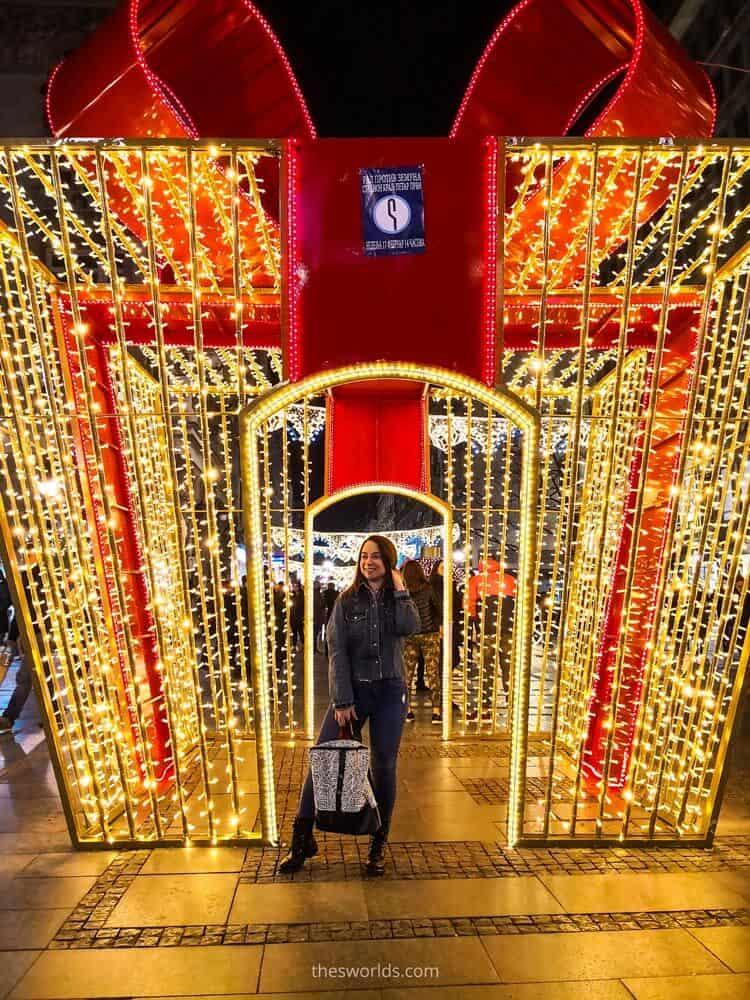 Girl standing beneath a christmas decoration in Belgrade