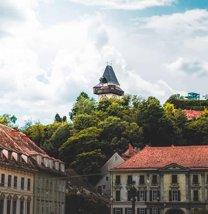 Clock tower surrounded with trees in Graz