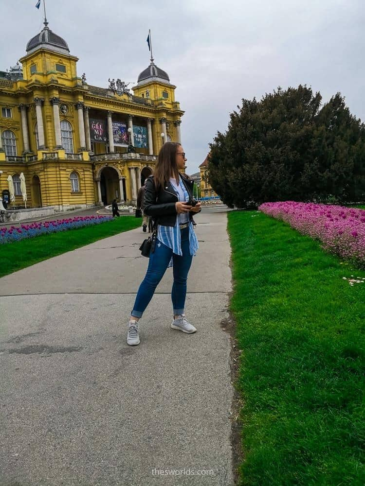 Girl posing in front of Croatian national theater in Zagreb