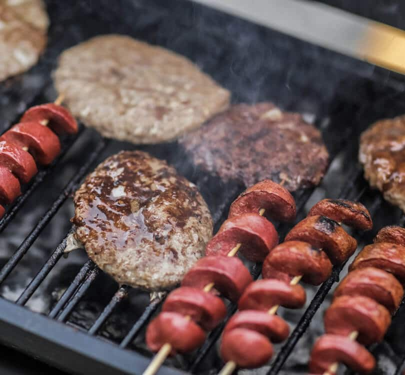 Sausages and hamburgers cooking on BBQ