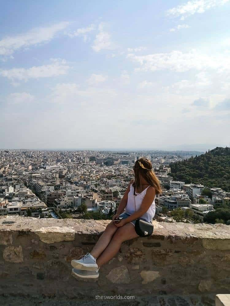 Girl looking at Athens city center while sitting on Acropolis walls