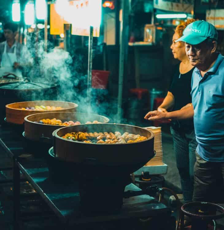 People cooking food at street market in Kuala Lumpur