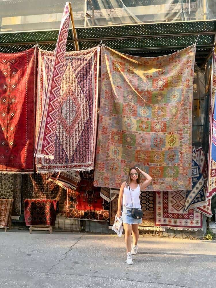 Girl posing in front of carpets in Athens