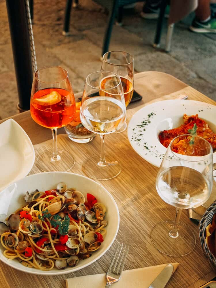 Couple eating pasta, seafood and drinking wine and water