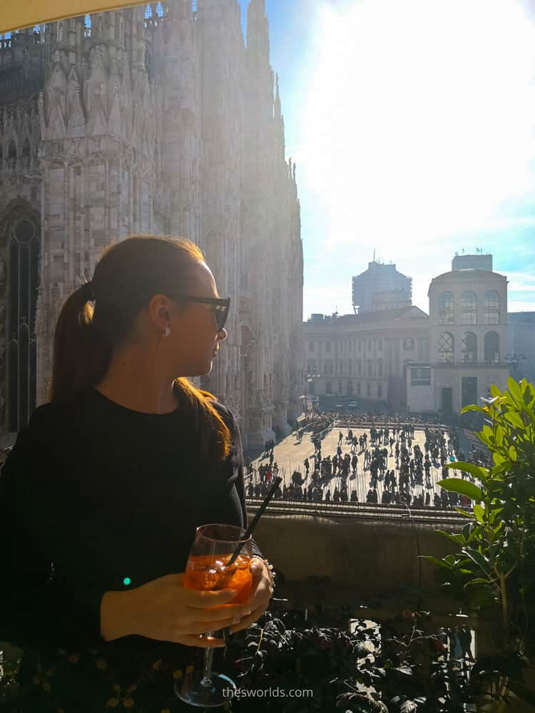 Girl looking from balcony drinking wine at people in Milan