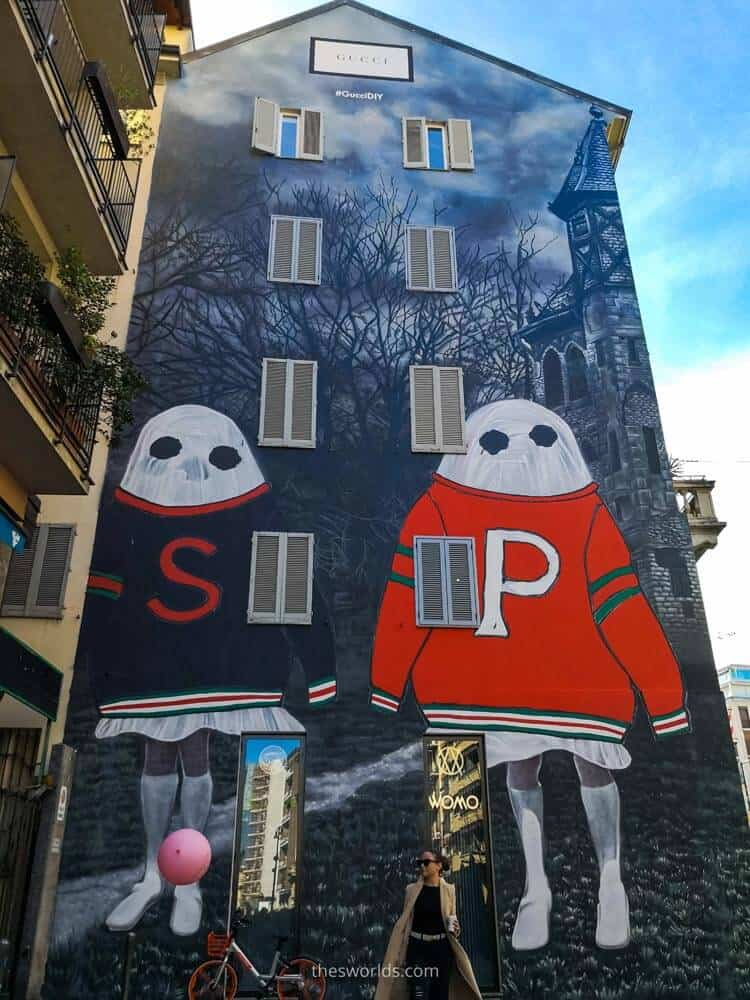 Two ghost graffiti on building in Milan with girl at the bottom of the building