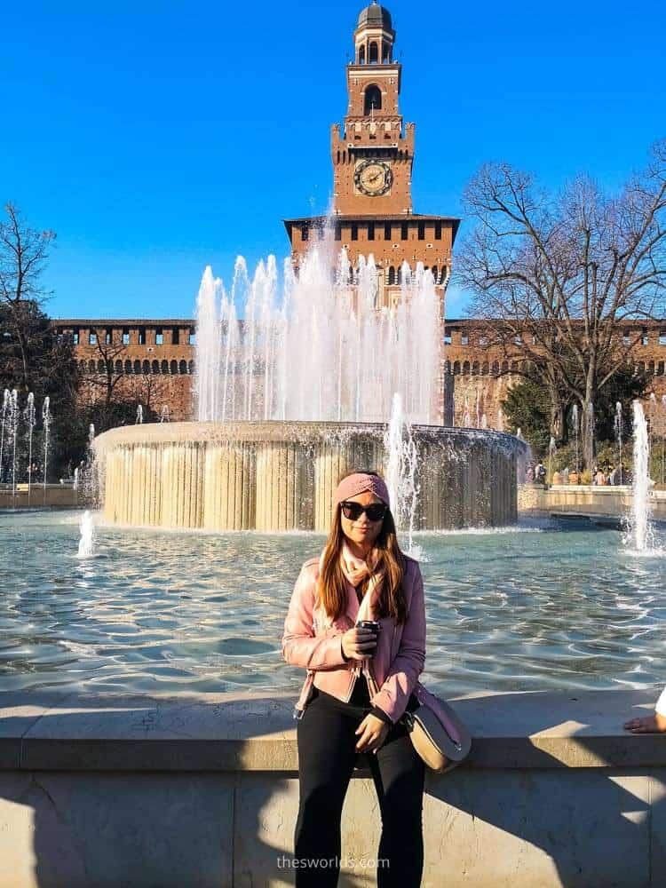 Girl sitting next to fountain at entrance to Sforzesco castle