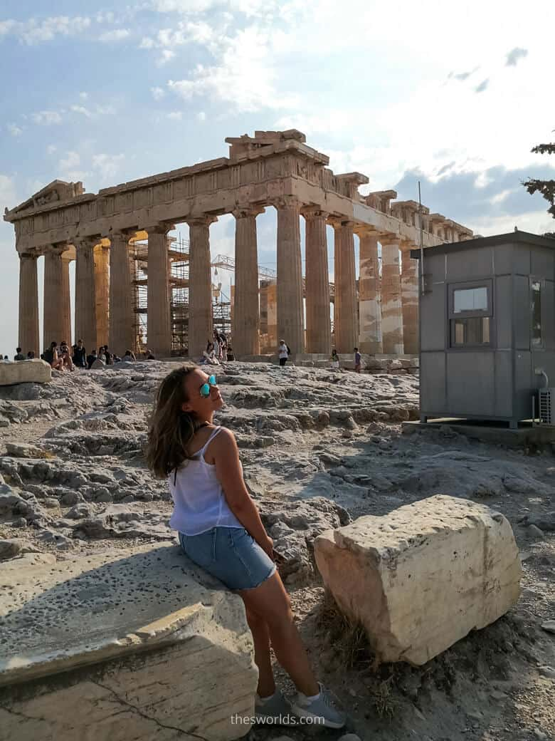 Girl sitting on a rock in from of Parthenon in Athens