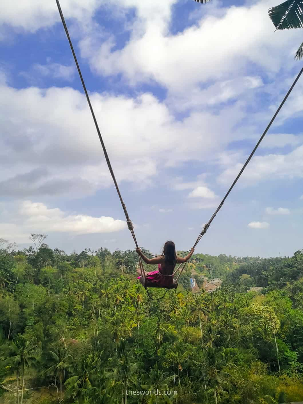 Girl swinging with forest in the background