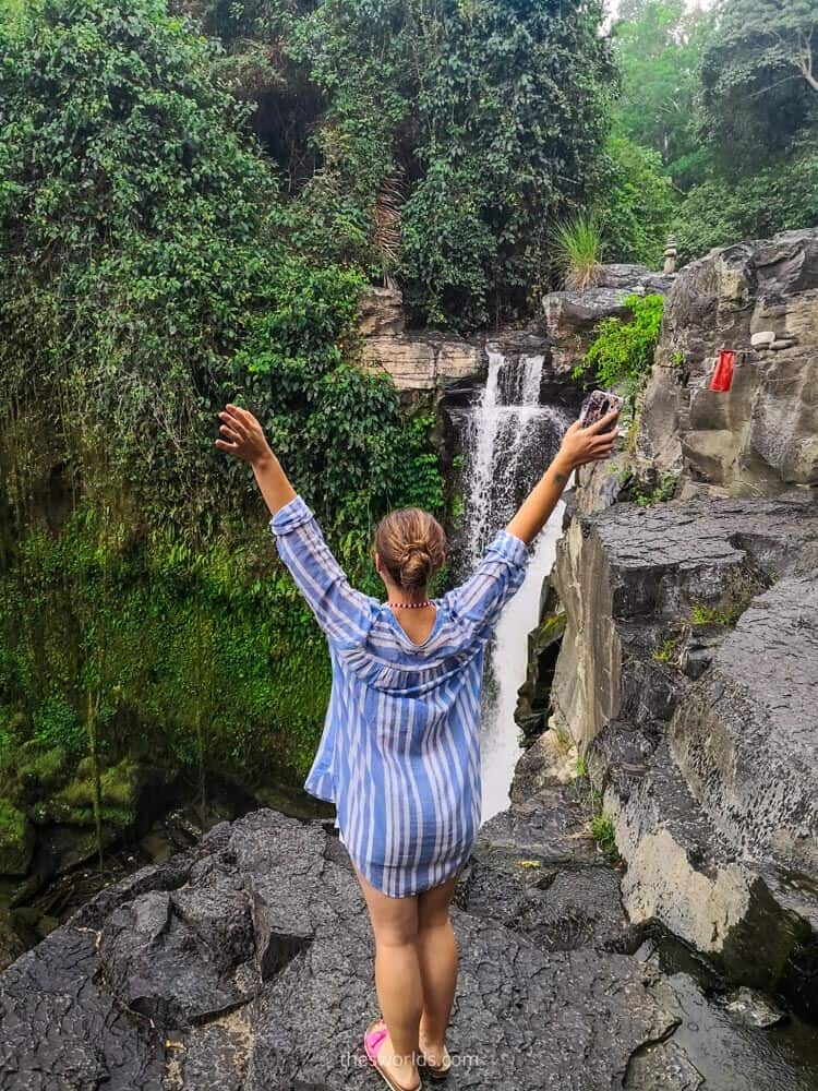 Girl standing at top of waterfall in Bali