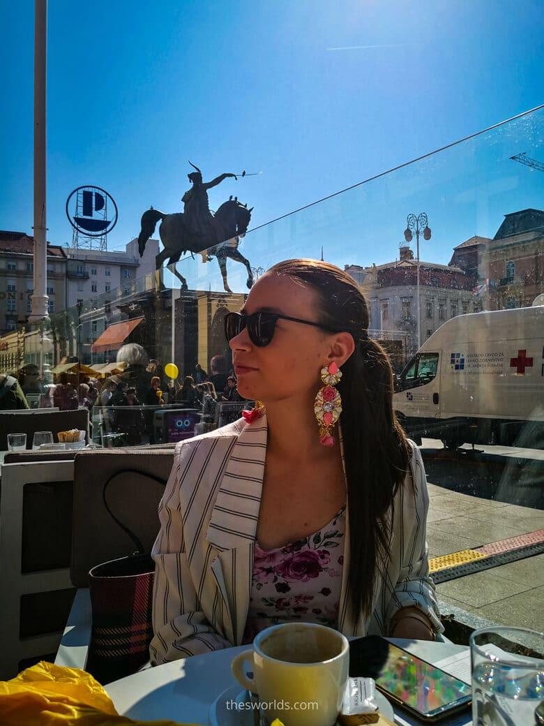 Girl drinking coffee at Ban Josip Jelacic square in Zagreb