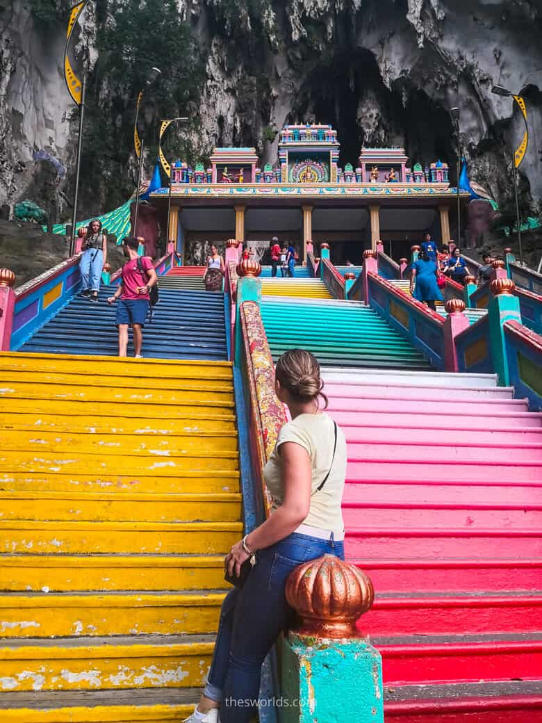 Girl sitting on stairs at entrance to Batu Caves in Kuala Lumpur