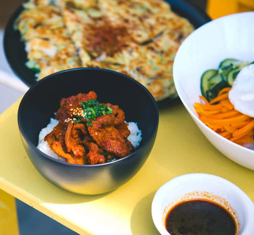 Multiple food dishes on table with rice and chicken in black bowl at beginning