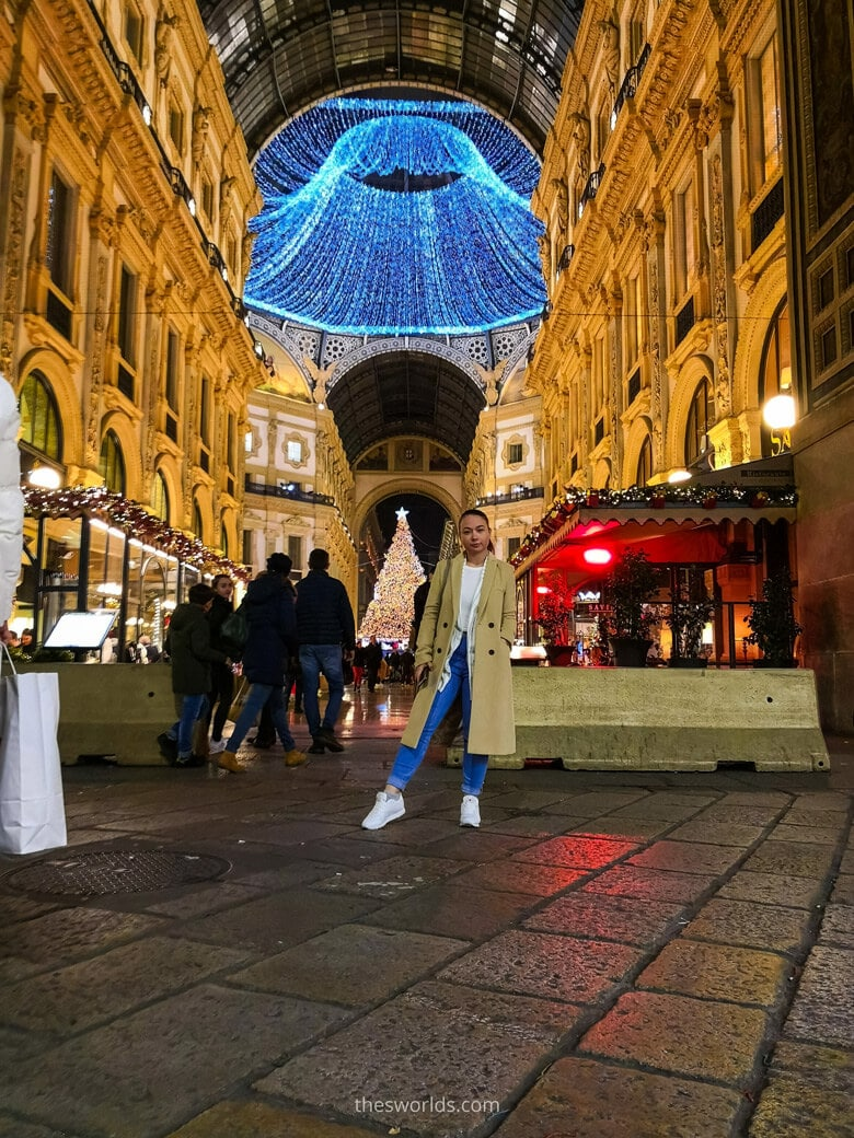 Girl standing at entrance to Galleria Vittorio Emanuele at night