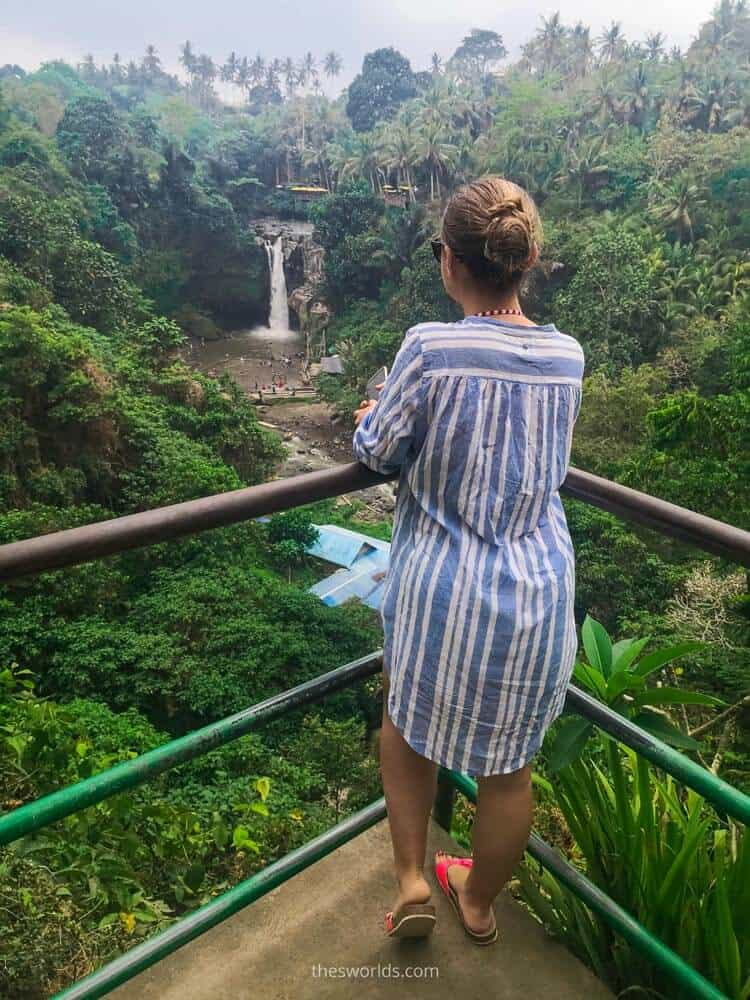 Girl standing on balcony looking at forest and waterfall