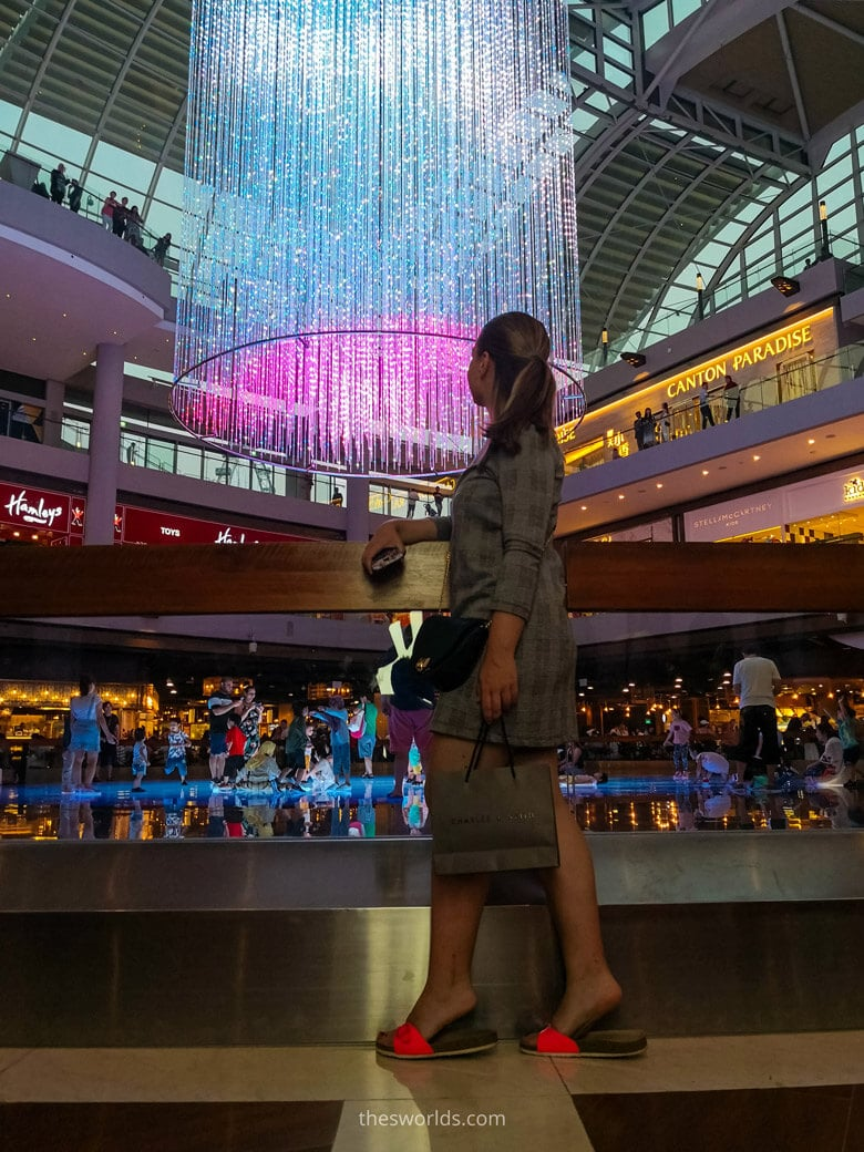 Girl looking at chandelier while people shop at Marina bay Shopping mall