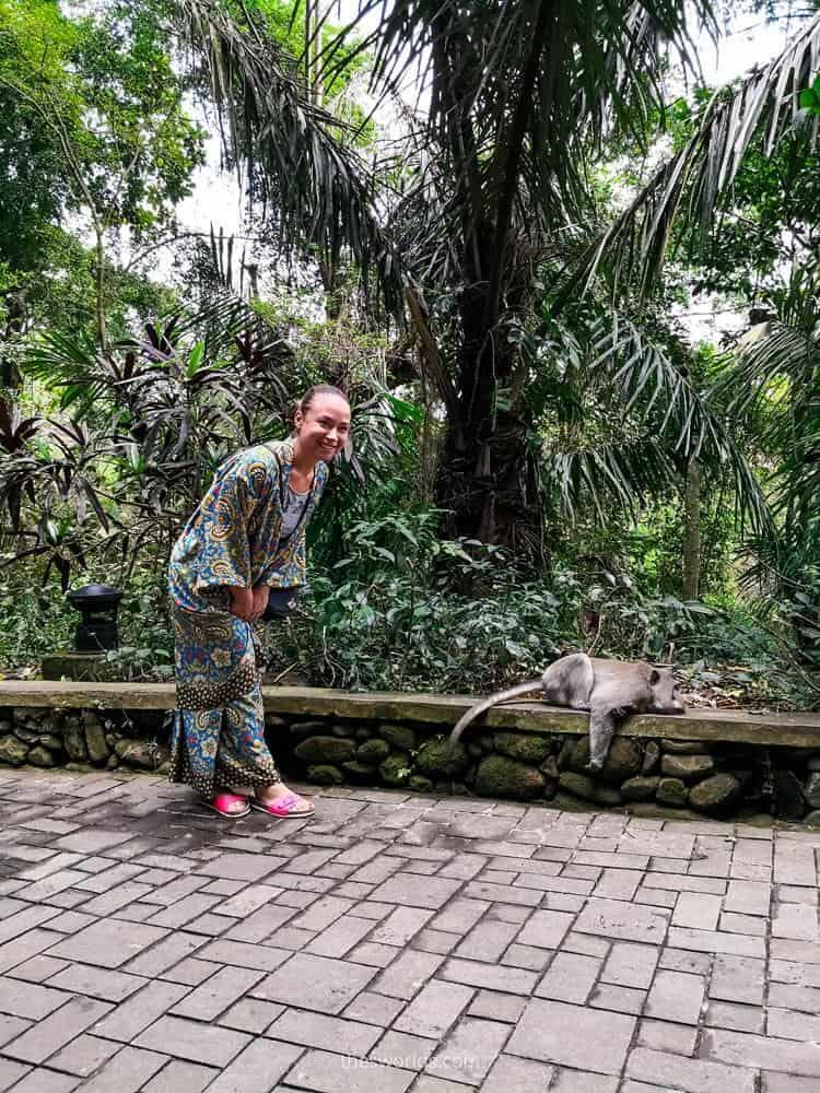 Girl posing with monkey lying next to her in Ubud