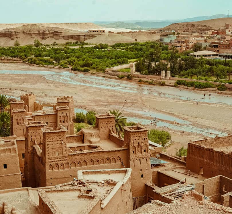 Old morocco building next to river with people