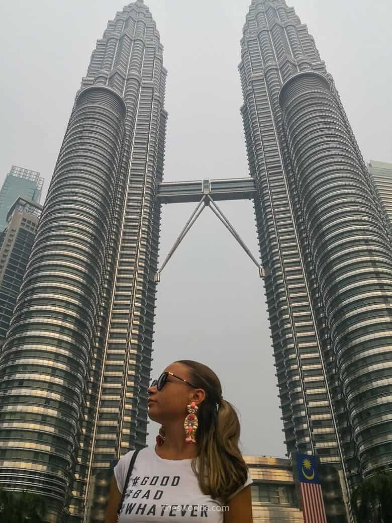 Girl standing in front of Petronas twin towers in Kuala Lumpur