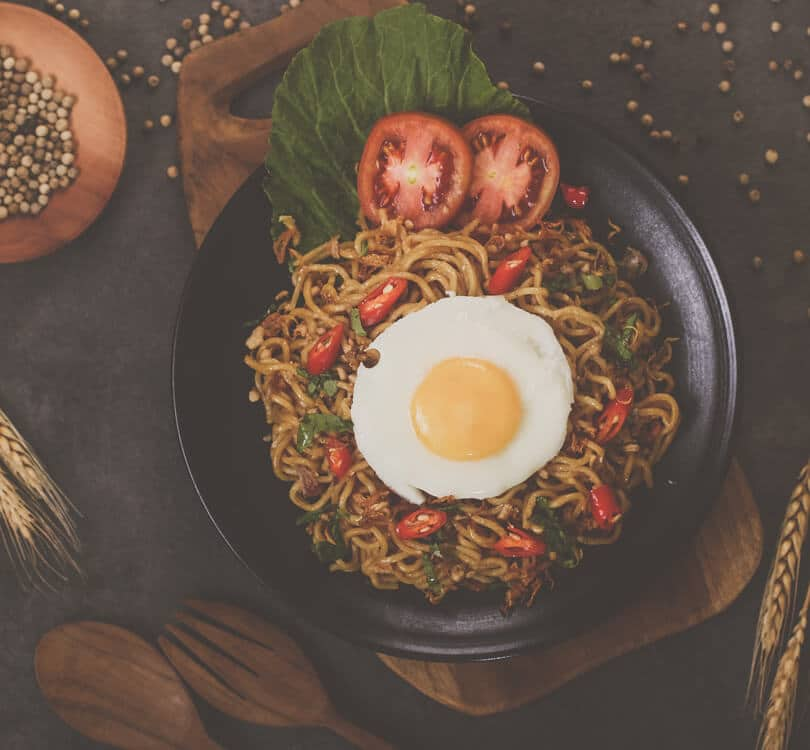 Spaghetti with egg and tomatoes on a black plate