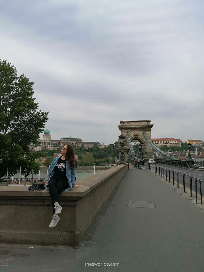 Girl sitting on Szechenyi Chain Bridge in Budapest