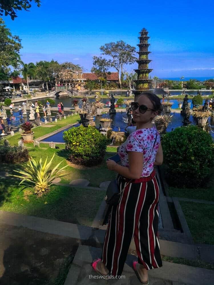 Girl posing at Taman Tirtagangga temple at Bali with fountain in the background