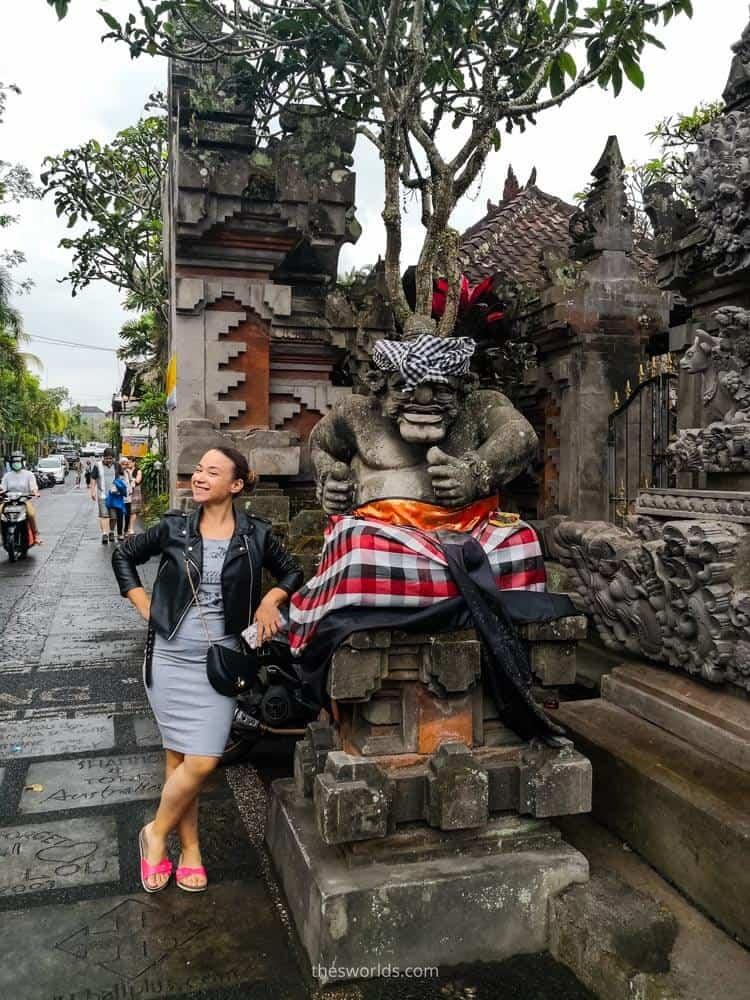 Girl posing next to statue at Ubud