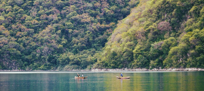 People in boats in lake next to tree mountain in Guatemala