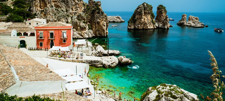 Beach with house and people in Sicily
