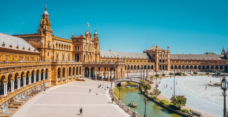 View of building and river under bridge in Seville