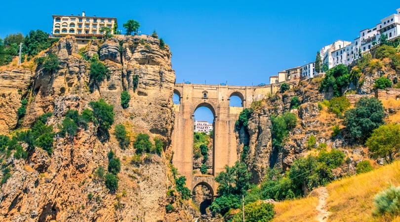 Building on a cliff standing next to a bridge in Spain
