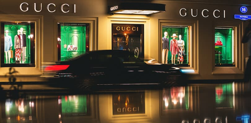 Gucci entrance at night with car passing