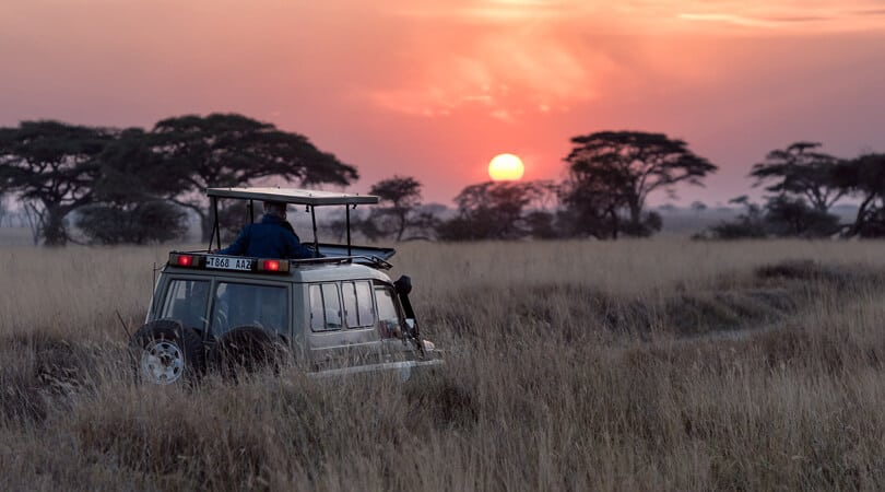People in a jeep looking at sunset at Serengeti National park