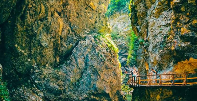 People looking at nature from a bridge in mountains in Slovenia