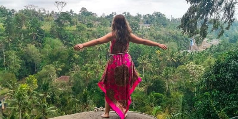 Girl looking at forest while standing on a rock in Bali mobile